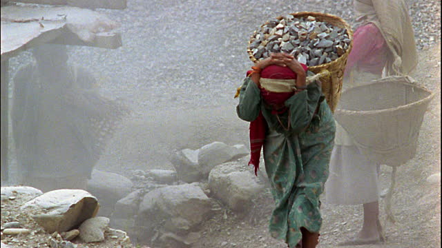woman carrying stones
